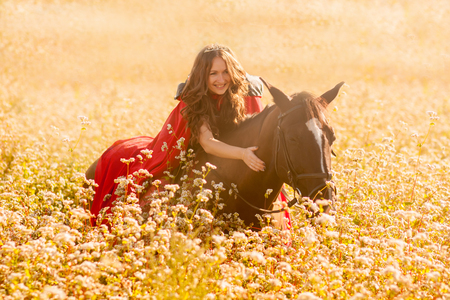 the queen on the horse. in the crown and cloak. jumps on a horse on a golden field Reklamní fotografie