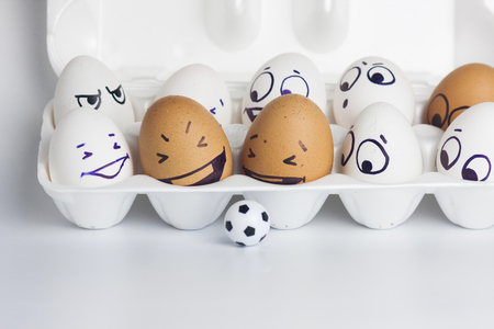 football fans are funny. Funny eggs with a face are playing a little ball. photo for your design