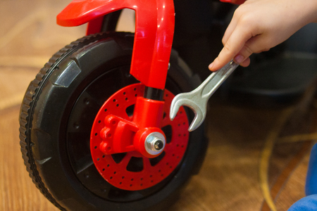 wheel repair key. childrens car service. play baby. horizontal photo. baby and motorcycle. future profession Stock Photo