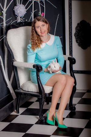 White rabbit in the hands of a beautiful girl sitting on a white throne. The Queen. Alice is a fairy tale.