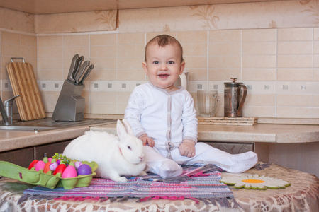 Easter white rabbit with a bow and a cheerful baby on the table. Easter menu. bright colored eggs in a green box and a snow-white rabbit on the table