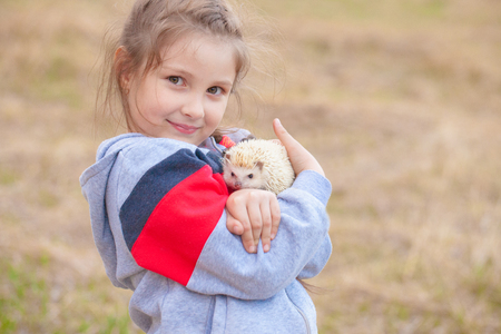 The concept of happiness. Little girl hugging a hedgehog. A child plays with a pet.