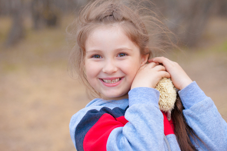 Smile concept. The girl laughs and plays with a hedgehog. The baby is holding a rodent.