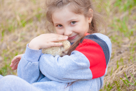 The concept of friendship between humans and animals. Little girl hugging a hedgehog. A child plays with a rodent.