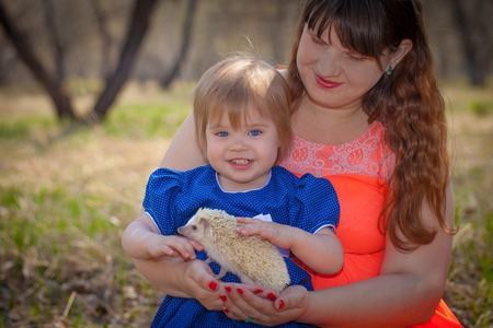Family concept. Mom and daughter are playing with a hedgehog. Little girl petting a rodent. Imagens