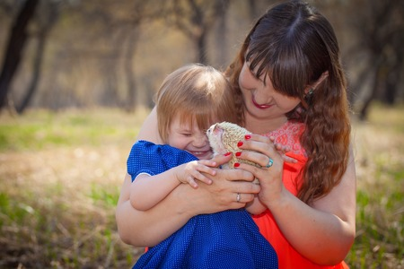 The concept of fun. Mom and daughter are playing with a hedgehog. The little girl laughs with happiness. Imagens