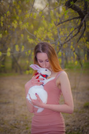 Beautiful girl kisses a rabbit. A woman is holding a white hare. Fluffy rodent and man.