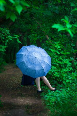 The concept of mystery. The girl hid behind a blue umbrella. Woman levitates. Imagens