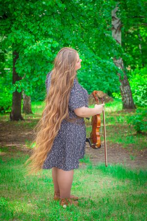 The concept of inspiration. Beautiful girl with long hair holds a violin in her hands. Full girl in full growth.?