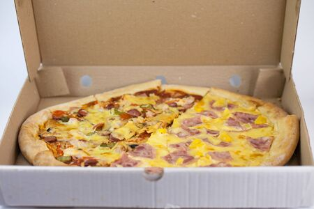 Appetizing and tasty pizza in a cardboard box on a white background 免版税图像