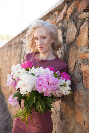 Beautiful girl with a bouquet of peonies. Skin care