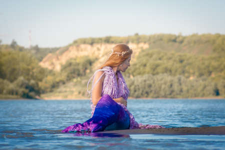 Girl with a mermaid tail on the river bank. Mystical and fairytale heroine. A sensation on vacation. The water has cleared