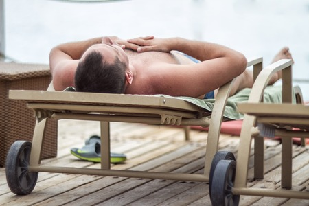 out of context: A man lies on a lounger on the beach Stock Photo