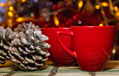 arbol de cafe: Dos tazas rojas en la stode cerca de los conos de pino abeto y árboles de Navidad
