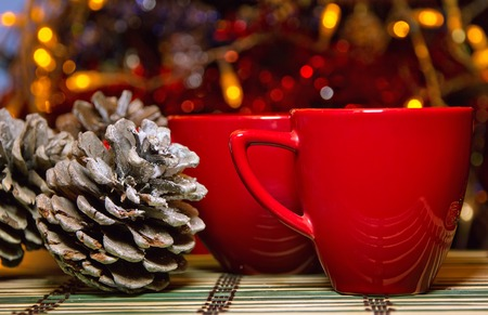 party table: Two red cups on the stode near spruce pine cones and Christmas tree
