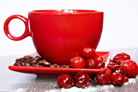 droop: Red Cup on a saucer with cowberries and cranberries on a white background