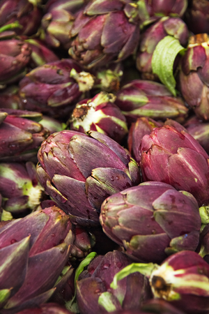 Many ripe artichokes vegetables lie on the counter