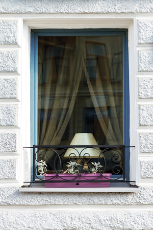 lattice window: Window with a table lamp and decorative lattice with flowers Stock Photo