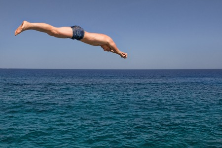 Young man stripped jumps into the sea in a sunny day