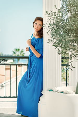 Girl in blue dress standing by Greek columns and olive tree Stock Photo