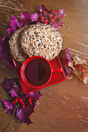Red Cup with cookies, autumn leaves and berries Banco de Imagens