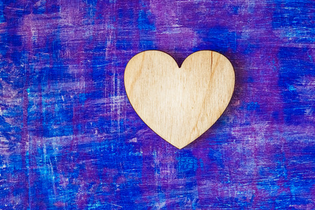 Wooden heart on abstract lilac painted wooden wall witn strokes Stock Photo