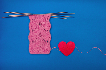 pink socks made of wool, knitted with an openwork pattern with red wooden heart on blue background