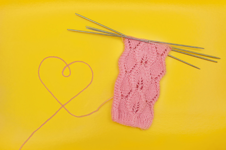 pink socks made of wool with heart shape made of thread, knitted with an openwork pattern on four knitting needles on yellow background