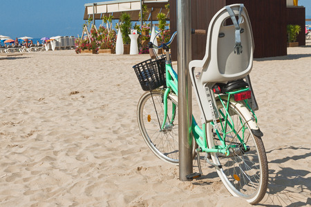 green bike with black shopping basket and gray baby chair is standing at the metal pole on beach on sunny day