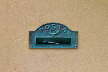 old green mailbox with the inscription in Italian word posta means mail and pipe on yellow wall of house, Porto Venere, Italy Banque d'images