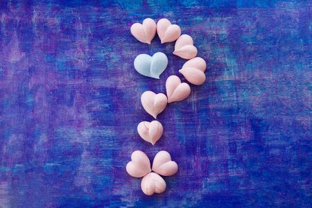 pink and one blue meringue hearts in the form of a question mark on painted purple background view from above Imagens - 128511528