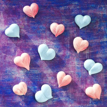 pink and blue meringue hearts on painted purple background diagonally, square