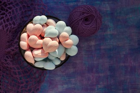 pink and blue meringue hearts on painted purple background with stripe and violet cotton mesh, and ball of cotton thread with copy space Imagens - 128512362