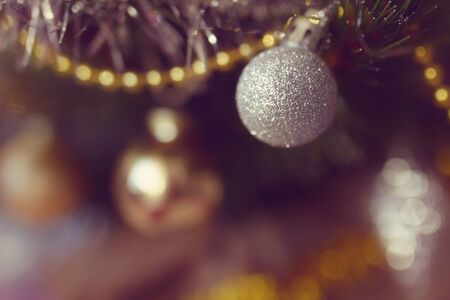 white brightening christmas ball close-up with yellow gerland on a branch in the Christmas and New Year holiday