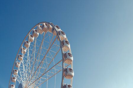 white metal ferris wheel with booths with windows against a blue sky, bottom view