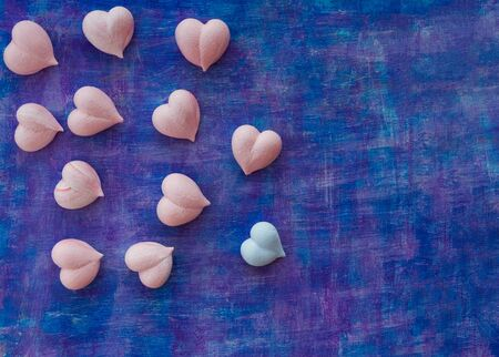 pink and one blue meringue hearts on painted purple background diagonally, copy space Imagens - 128515022