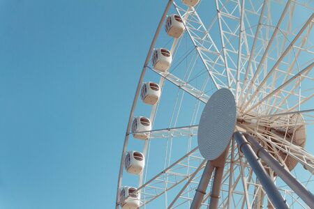white metal cabins of ferris wheel with booths with windows against blue sky, bottom view