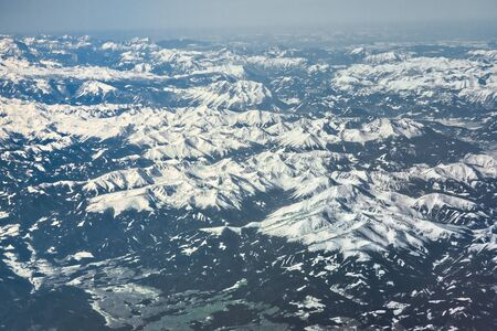 Blue Alps mountains with snowy white peaks from an airplane Stock fotó