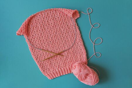 pink sweater made of cotton knitted with an openwork pattern on circular knitting needles on turquoise background