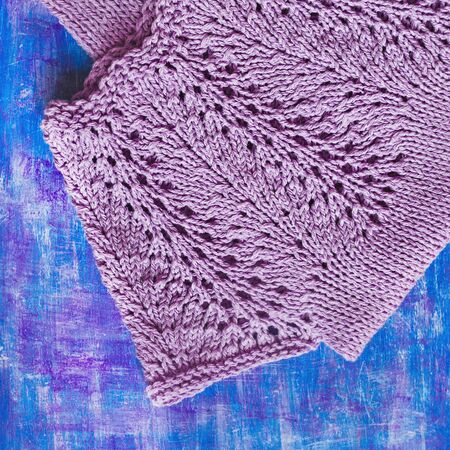 knitting needles violet-colored baby dress with lace yoke on lilac painted wooden background