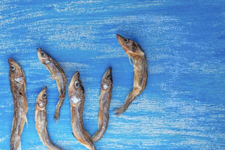 dried smelt fish six pieces on a wooden painted background similar to the sea Imagens