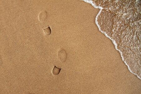 footprints of walking man s shoes on yellow sand near sea surf, copy space