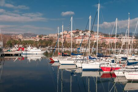 View of promenade and houses city of La Spezia in Italy from blue ligurian sea and harbor with white yachts on sunny day