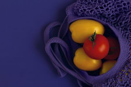 one red and two yellow tomatoes are in purple cotton netted bag on lilac background on the right, copy space