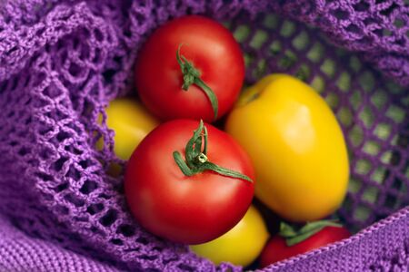 three red and yellow tomatoes are in n purple cotton netted bag top view close up