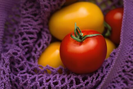 red fresh and yellow tomatoes are in n purple cotton netted bag close up