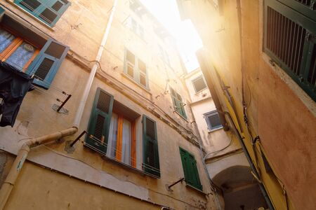 View of old close yellow courtyard with green wooden window shutters in Riomaggiore, Cinque Terre, Liguria, Italy