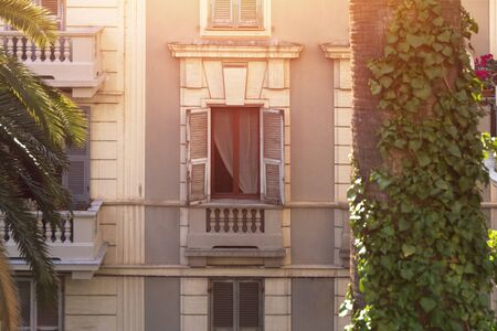 old brown wooden windows with open shutters, on sunny day on yellow wall with palm tree and curly tropical leaves in Italy