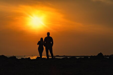 silhouettes of man and woman on a dais stand with their backs and look at sea sunset