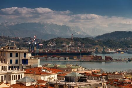 freight seaport on a background of alpine mountains where a marble quarry and urban traditional Italian houses in La Spezia, Italy